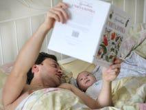 Papá con un bebé en un pesebre Foto de archivo