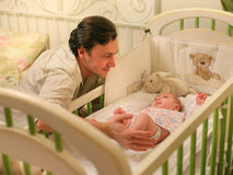 Papá con un bebé en un pesebre Fotos de archivo libres de regalías