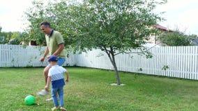 Papá con un hijo de cuatro años que juega la bola, fútbol, en la yarda en un césped verde, en el verano almacen de metraje de vídeo