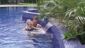 Papá con una pequeña nadada de la hija en la piscina almacen de video