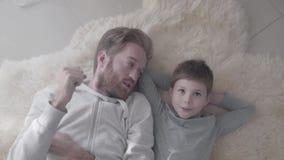 Papá de la diversión con la barba y su pequeño hijo que miente en la alfombra blanca de la piel y tener conversación interesante  metrajes