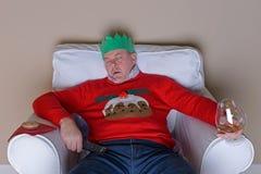 Papá dormido en una silla el día de la Navidad fotografía de archivo