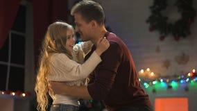 Papá dulce y muchacha que abrazan cerca de árbol chispeante de Navidad, teniendo placer junto almacen de metraje de vídeo