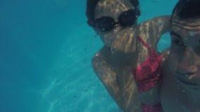 Papá e hija en la piscina subacuática el adolescente del hombre y de la muchacha se baña en submarino de la piscina