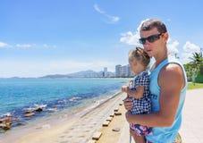 Papá e hija que juegan en la 'promenade' por el mar hombre joven, niña Fotos de archivo