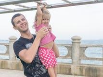 Papá e hija que juegan la 'promenade' por el mar hombre joven, ejecución de la niña en la barra Imagen de archivo libre de regalías