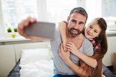 Papá e hija que presentan para el selfie Imagenes de archivo