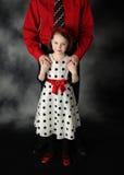 Papá e hija vestidos encima de las manos de la explotación agrícola Fotografía de archivo libre de regalías