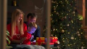 Papá e hijo de la mamá en los regalos abiertos de la Navidad en casa que se sientan en el sofá en el interior de la Navidad Hogar almacen de metraje de vídeo