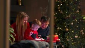 Papá e hijo de la mamá de la familia en los regalos abiertos de la Navidad en casa que se sientan en el sofá en el interior de la almacen de metraje de vídeo