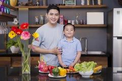 Papá e hijo en la cocina con mucha fruta y verdura fotos de archivo