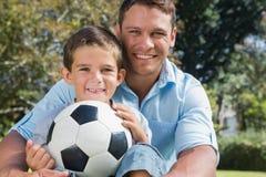 Papá e hijo felices con un fútbol en un parque Imagen de archivo