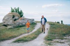 Papá e hijo que corren en el campo con el perro Foto de archivo