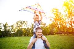 Papá e hijo que juegan con la cometa Imagen de archivo libre de regalías
