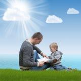Papá e hijo que leen un libro en la naturaleza Fotos de archivo