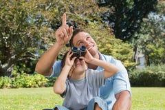 Papá e hijo que miran el cielo con los prismáticos Imagen de archivo libre de regalías