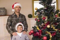 Papá e hijo que presentan cerca del árbol de navidad Fotografía de archivo