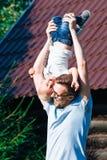 Papá e hijo que se divierten en el jardín Imagen de archivo libre de regalías