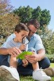 Papá e hijo sonrientes que examinan la hoja con una lupa Fotos de archivo libres de regalías