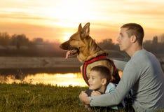 Papá e hijo y pastor alemán en naturaleza que miran la puesta del sol Imágenes de archivo libres de regalías
