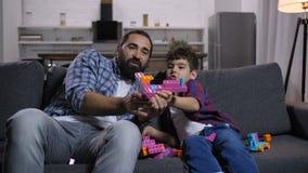 Papá emocionado y niño que juegan con el juguete colorido metrajes