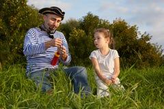 Papá en juego del pirata e hija en hierba imagen de archivo libre de regalías