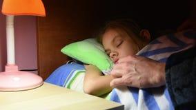 A papá endireitou a cobertura tem adormecido caído e beija sua filha girada fora da lâmpada de mesa pela cama vídeos de arquivo
