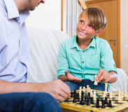 Papá feliz e hijo adolescente que juegan a ajedrez Fotos de archivo libres de regalías