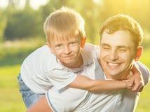 Papá feliz e hijo que abrazan y que ríen en naturaleza del verano Fotos de archivo libres de regalías