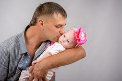 Papá feliz que besa a una hija de dos meses del bebé foto de archivo