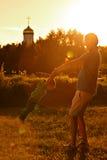 Papá feliz que juega con su hijo en el parque en un fondo de la iglesia Imágenes de archivo libres de regalías