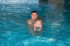 Papá hermoso feliz joven con su hija que juega en una piscina en un parque del agua en el agua alrededor de ellos para desnudar y Fotos de archivo libres de regalías
