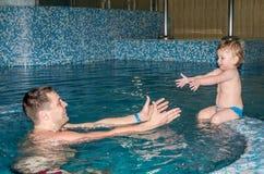 Papá hermoso feliz joven con su hija que juega en una piscina en un parque del agua en el agua alrededor de ellos para desnudar y Imágenes de archivo libres de regalías