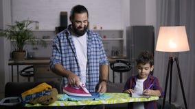 Papá hogareño que ayuda al hijo con el schoolwork almacen de metraje de vídeo