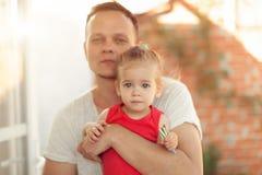 Papá joven que lleva a cabo y que abraza su pequeño concepto de familia dulce de la hija sobre amor y cuidado fotos de archivo libres de regalías