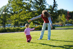 Papá joven y su pequeña hija que juegan el disco volador Imagen de archivo libre de regalías