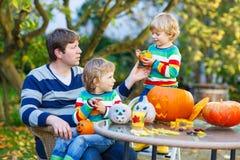 Papá joven y su pequeño hijo que hacen la Jack-o-linterna para Halloween Imagen de archivo libre de regalías