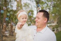Papá juguetón que detiene al bebé que disfruta de burbujas afuera en el parque Foto de archivo