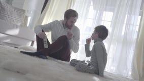 Papá juguetón que se sienta con su hijo en la alfombra y que sostiene el dinero El hombre y el muchacho pusieron un finger a la n almacen de video