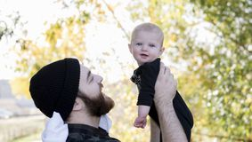 Papá milenario que detiene a la hija del bebé para arriba que muestra el afecto fotografía de archivo libre de regalías