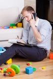 Papá multifuncional que habla en el teléfono Fotos de archivo libres de regalías