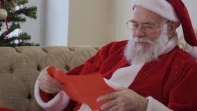 Papá Noel abre el sobre y comienza a leer la letra de la Navidad almacen de metraje de vídeo