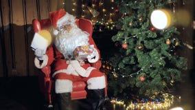 Papá Noel abre esencial de la Navidad cerca de la chimenea de la Navidad 4K metrajes