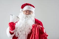 Papá Noel alegre que da el presente deseado Fotos de archivo