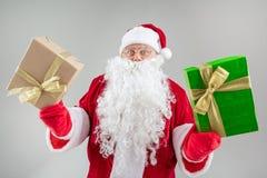 Papá Noel alegre que muestra presentes grandes Imagen de archivo libre de regalías