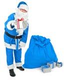 Papá Noel azul da un presente Fotos de archivo