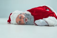 Papá Noel blanco rojo trabajó demasiado el concepto de la quemadura de la frustración que mentía en el piso aislado en el fondo b fotos de archivo libres de regalías
