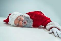 Papá Noel blanco rojo trabajó demasiado el concepto de la quemadura de la frustración que mentía en el piso aislado en el fondo b foto de archivo