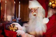 Papá Noel clásico que pone un regalo a la media de la Navidad Imagenes de archivo