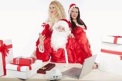 Papá Noel con dos ayudantes atractivos en su oficina Fotografía de archivo
